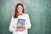 Happy schoolgirl with bowtie holding textbooks on blackboard