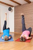 An image of some people doing yoga exercises - Eka Pada Setu Bandha Sarvangasana