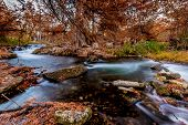 stock photo of guadalupe  - Beautiful Fall Foliage Surrounding the Silky Waters Flowing Down the Guadalupe River in Texas.