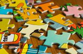 Children's Puzzle Scattered On A Wooden Table