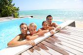 Happy family enjoying bath time in infinity pool