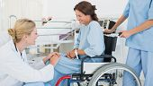 Side view of a doctor talking to a female patient in wheelchair at the hospital