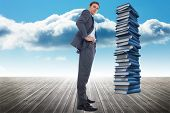 Serious businessman with hands on hips against stack of books against sky