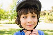Close-up portrait of a cute little boy wearing bicycle helmet