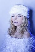 Beautiful young blond winter woman in a stylish white fur ensemble standing dreaming with a wide eye