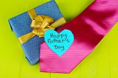 Happy Fathers Day tag with gift boxes and tie, on wooden background