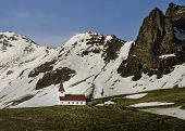 Red-steepled church surrounded by alpine mountains in the town of Vik y Myrdal in Iceland