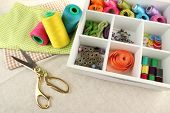 Tools and materials for sewing in box on fabric background