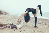 Young beautiful gymnast posing on the summer beach