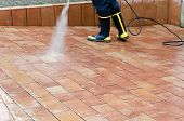 stock photo of water jet  - Workers cleaning with high pressure cleaner the entrance of a car garage
