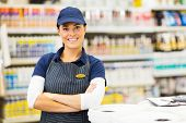 beautiful young female supermarket worker with arms crossed