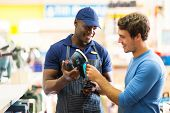 friendly hardware store worker showing customer a sander