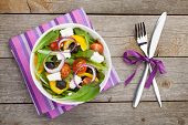 Fresh healty salad on wooden table and silverware