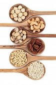 Nut varieties of hazelnut, cashew, pistachio, pecan, pine kernel and chopped almonds in olive wood s