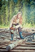 The young woman in wood saws a tree a chain sawwith a retro effect