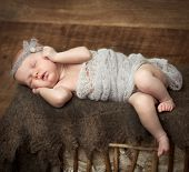 cute little newborn girl sleeping on a cot. retro style