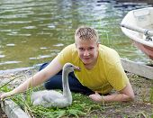 The teenager near a baby bird of a swan on the bank of the lake