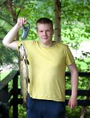 The young man the fisherman with the caught pike
