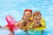 stock photo of one piece swimsuit  - Children sitting on inflatable ring in swimming pool - JPG