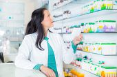 Pharmacist with prescription in front of medicines at drugstore