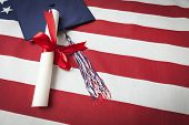 Graduation Cap with Tassel and Red Ribbon Wrapped Diploma Resting on American Flag.