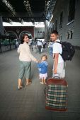stock photo of family vacations  - Happy family with little girl at railway station - JPG