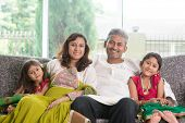 Indian family at home. Asian parents and children living lifestyle, sitting on couch indoor smiling