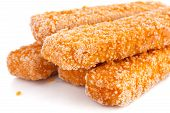 Frozen bread crumbed fish fingers on white.
