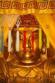 Golden statue of Buddha behind coloured tassels