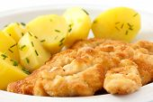 Golden fried schnitzel with boiled potatoes and chives.