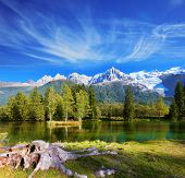 City park in the Alpine resort of Chamonix. Cold lake surrounded by trees and snow-capped mountains