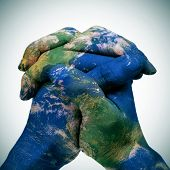 world map in the clasped hands of a man forming a globe (Earth map furnished by NASA)