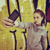 Happy attractive girl with smart phone takes photo of herself against urban grunge graffiti wall, toned.