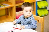 Little Child Boy Drawing With Colorful Pencils In Preschool At The Table In Kindergarten