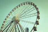 Retro Style Image Of A Ferris Wheel Against Blue Sky