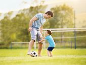stock photo of football pitch  - Young father with his little son playing football on football pitch - JPG