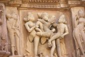 stock photo of kama  - Sculptures of loving couples illustrating the Kama Sutra on walls of Kandariya Mahadeva Temple at Khajuraho in India Asia - JPG