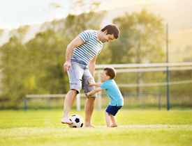 foto of football pitch  - Young father with his little son playing football on football pitch - JPG