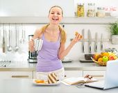 Happy Teenager Girl Eating Toast With Chocolate Cream In Kitchen