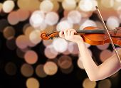 Young girl's hands with classical violin on bright background