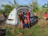 A Family In Front Of Their Emergency Shelter Tent
