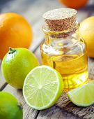 Citrus Essential Oil And Slice Of Orange, Lemon And Lime Fruits On Old Table