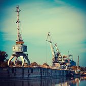 Working Cranes For Cargo At The Shipyard Docks In River Port.