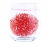 Tomato in glass of water isolated on white