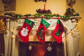 Toned Photo Of Three Red Christmas Socks Hanging On Fireplace