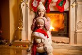 Portrait Of Two Beautiful Girls In Sweaters Sitting At Fireplace At House