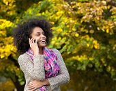 Young Woman Laughing Outdoors With Mobile Phone
