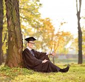 Graduate student sitting by a tree in a park shot with tilt and shift lens