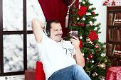 Mature Man Listening To Music On Headphones  Near Christmas Tree