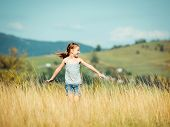 cute little girl runs through a beautiful meadow in the mountains.